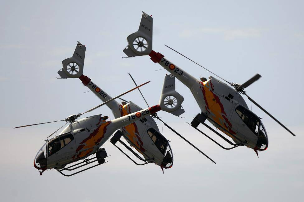 """Eurocopter EC120 Colibri helicopters from the Spanish Air Force's aerobatic team """"Patrulla Aspa"""" fly over La Malagueta beach during a military operational exhibition in Malaga"""