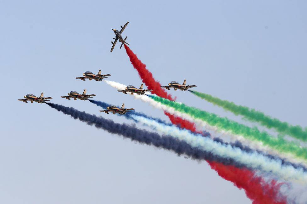 Aerobatic aircrafts emit coloured smoke trails as they perform during an airshow at the Abu Dhabi Air Expo