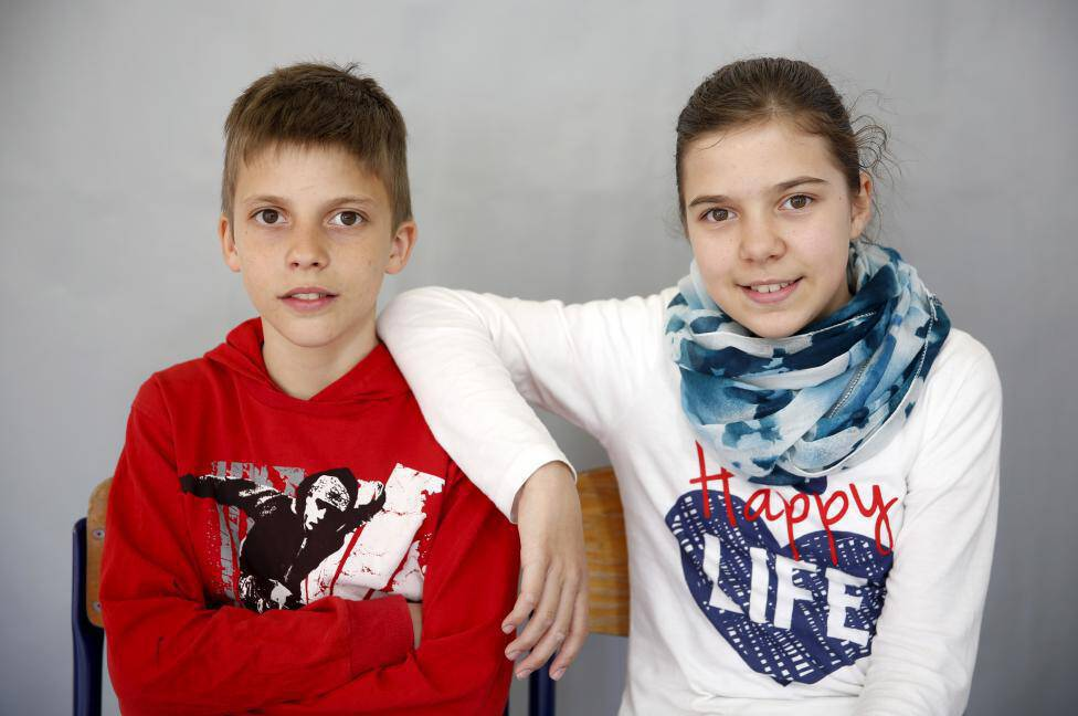Twins Almina and Almin Duranovic pose for a portrait in primary school in Buzim